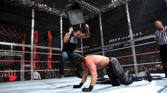 Dean Ambrose hits Rollins with a chair